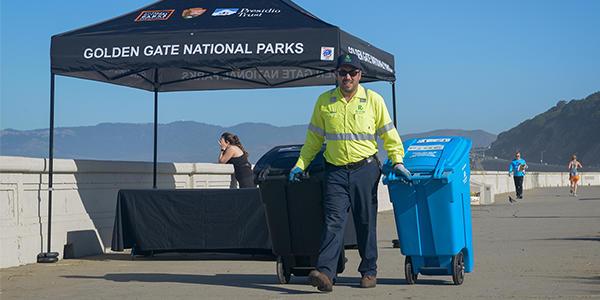 Recology worker walks trash bin down sidewalk at Ocean Beach in San Francisco.