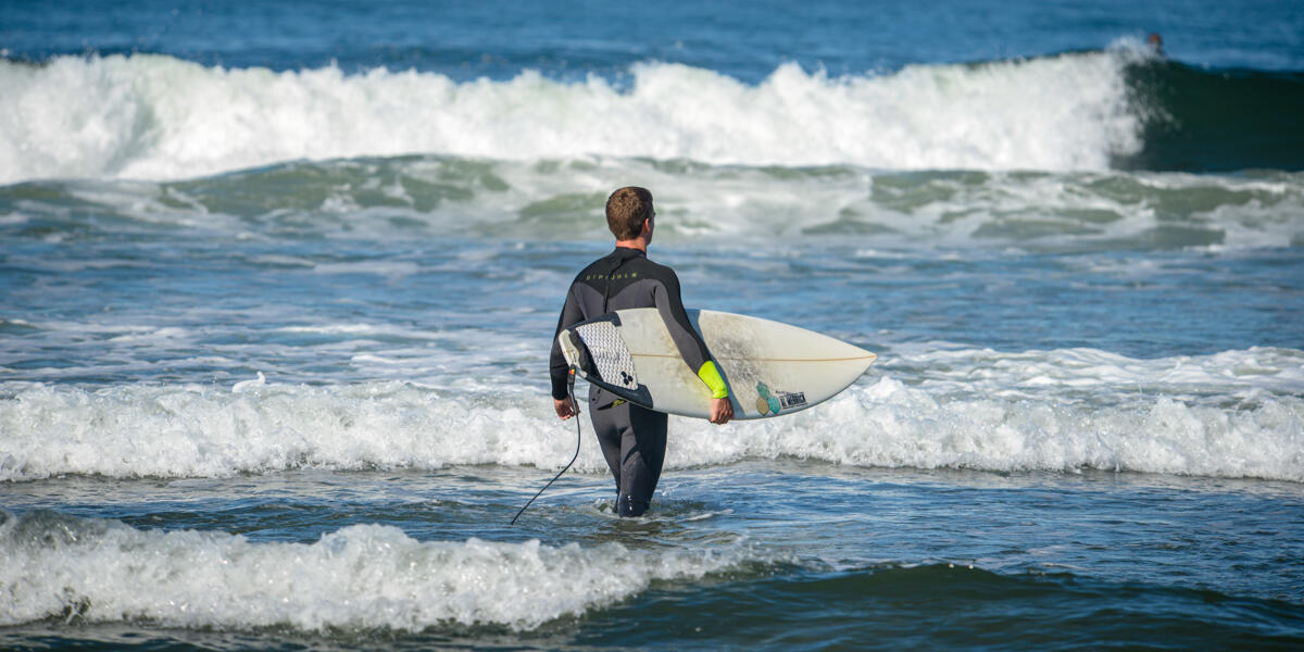 A surfer surveys the blue water and waves at Ocean Beach