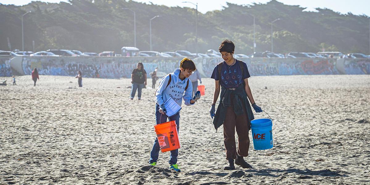 Two volunteers on trash pick up walk down Ocean Beach with buckets.