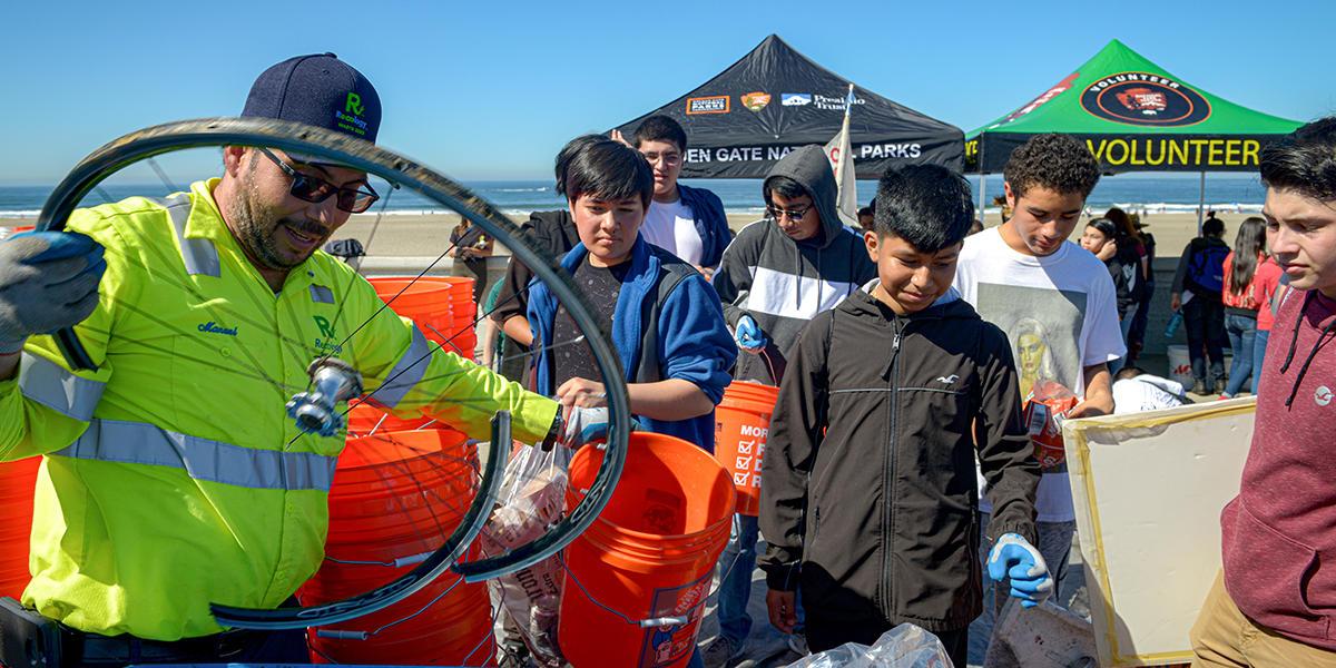 Reology worker puts bicyle wheel in trash bin. Taken during California Coastal Cleanup Day in Ocean Beach in San Francisco.