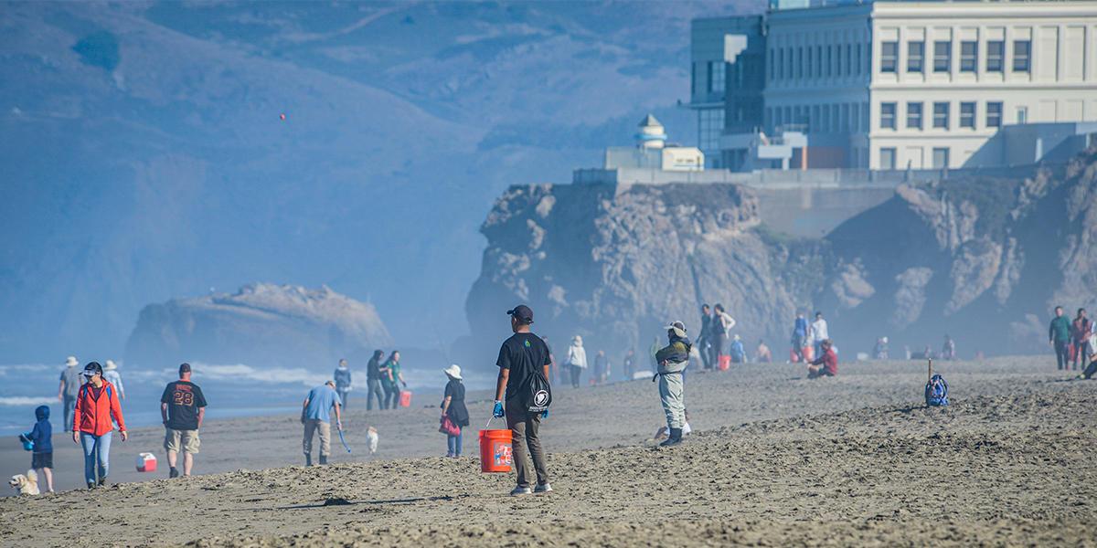 Crowd of volunteers on trash pickup duty on Ocean Beach in San Francisco.