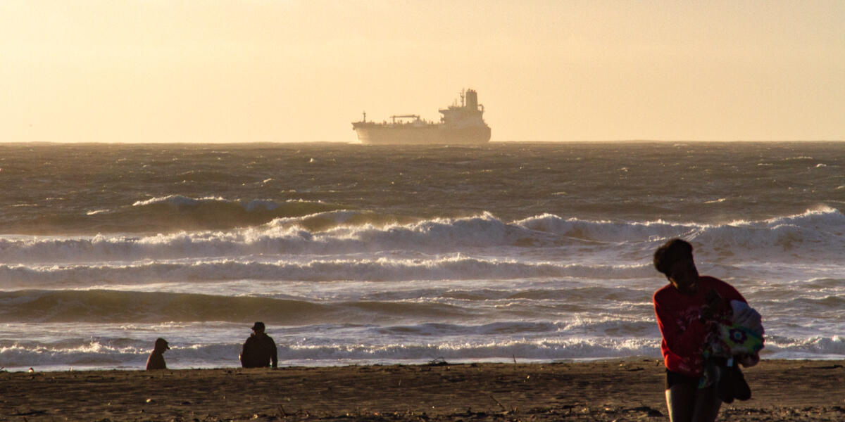 A large ship floats over the waves, along the horizon of Ocean Beach as park visitors enjoy the view of a sunset.