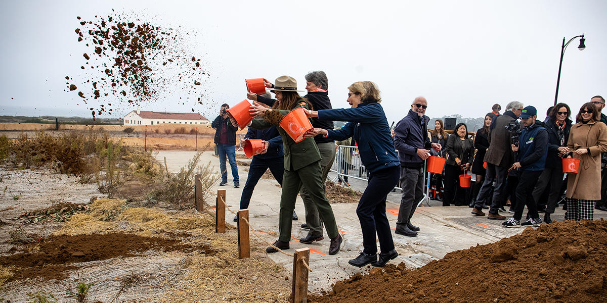 Three people throw buckets of dirt in the Presidio.