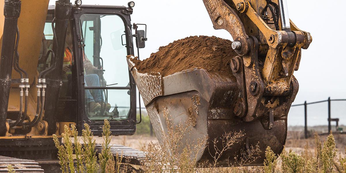 Excavator with dirt in bucket.
