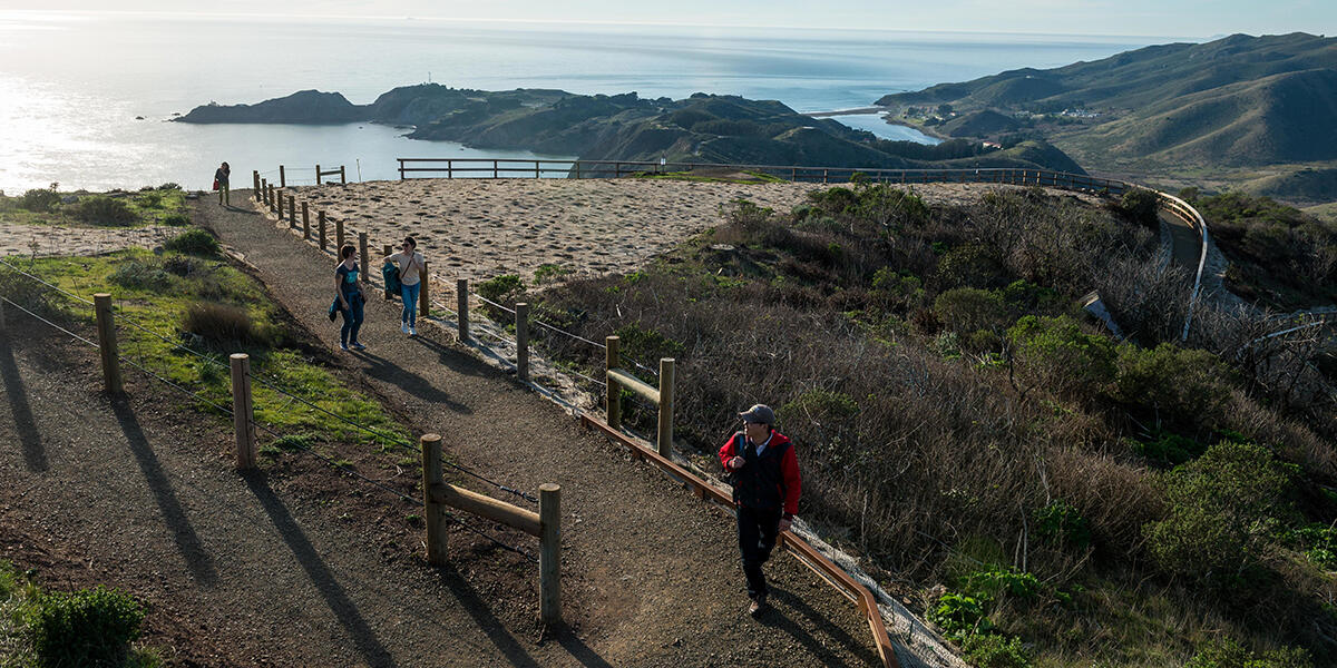 Hikers explore a newly built segment of the Hawk Hill Trail