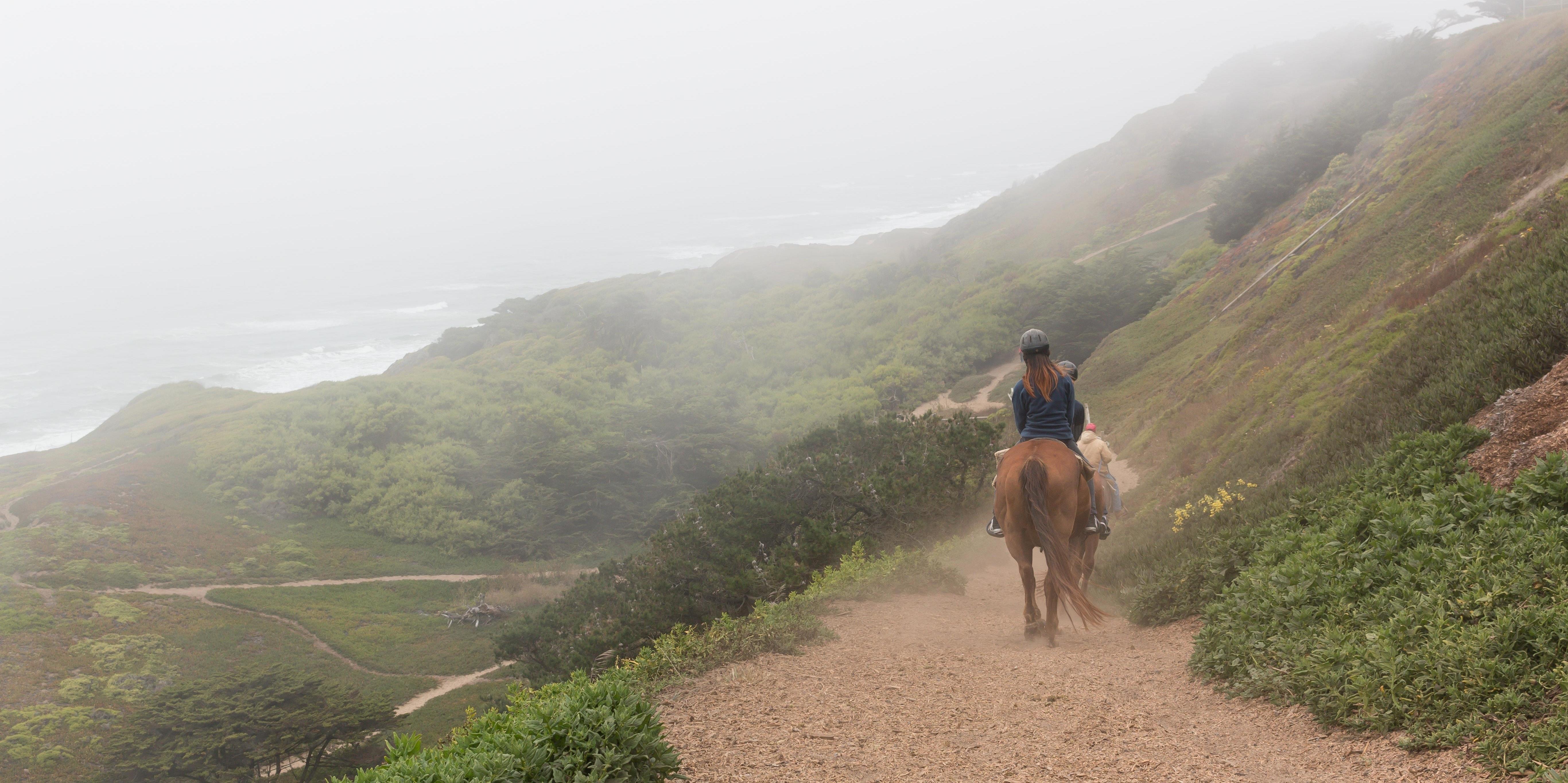 Equestrians ride through foggy Fort Funston