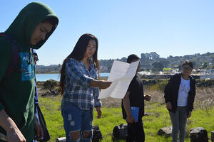 A group of four high school students stand in a line outdoors while leading a presentation about the natural environment