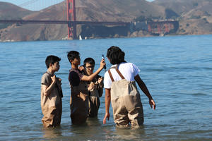 a small group of high school students learn to use environmental testing tools with an educator from the Crissy Field Center