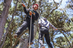 Two youth at the top of a ropes course