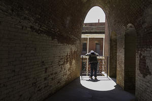A dark hall leads to a person looking down through a sunny archway on one of Fort Points upper levels
