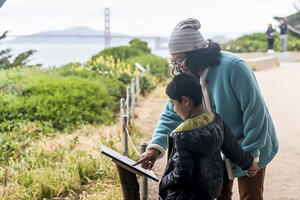 A family checks out a StoryWalk at Lands End in San Francisco.