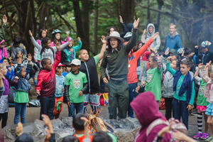A National Park Service Ranger leads a large group of smiling children in an interactive story