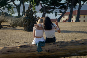 Couple sits on felled tree looking towards the Golden Gate Bridge