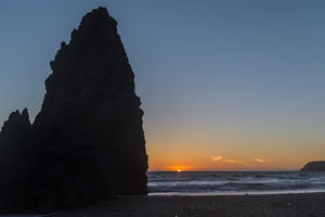 Sunset on the horizon with mitten-shaped rock formation on left.