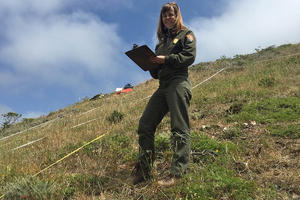 Alison Forrestel looks up for a smile while holding a clipboard among vegetation plots in a hilly grassland habitat.