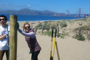 Trail Crew volunteers help install fence posts at Baker Beach.