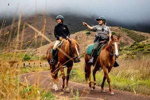 Lainie Motamedi, left, and Park Ranger Katlyn Grubb ride out from the Horse Mounted Patrol Stables in the Marin Headlands.