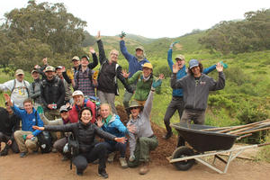 A group of volunteers joyfully pose after working outside on a trail