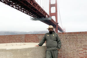 NPS Ranger Erick Cortes stands in front of the Golden Gate Bridge at Fort Point Historic Site.