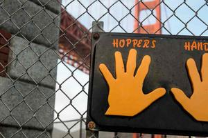 "Sign labeled ""Hopper's Hands"" on a fence with the Golden Gate Bridge behind."