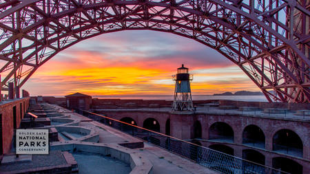 Lighthouse at Fort Point during sunset with Golden Gate Bridge arching above