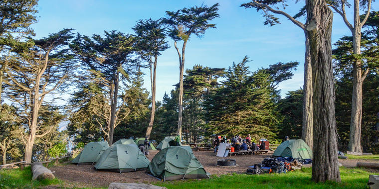 A group of adults sit outside on a sunny day eating lunch at a picnic bench under eucalyptus trees while surrounded by camping tents