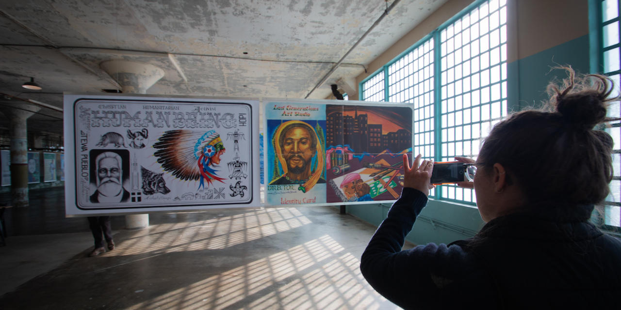 Woman takes photo of Future IDs display in the New Industries Building on Alcatraz.