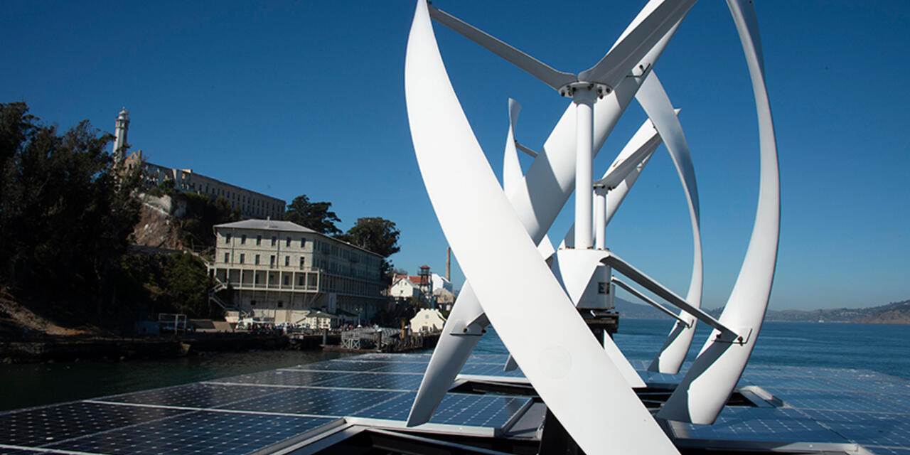 View of wind turbines and solar panels from atop an Alcatraz cruises boat.