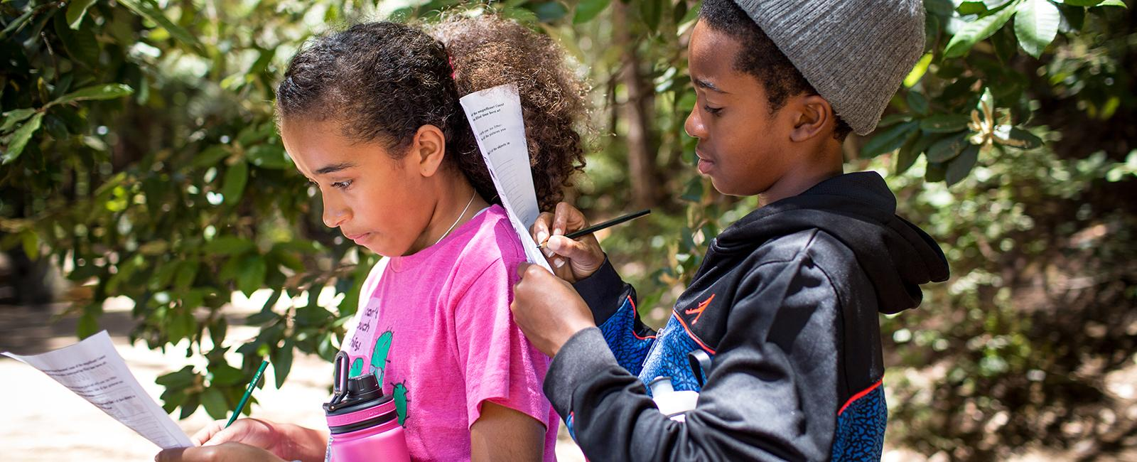 Children take a nature quiz during their hike with Latino Outdoors to Muir Woods National Monument