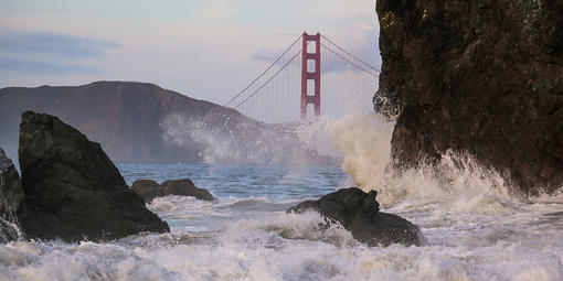 Waves crash before the Golden Gate Bridge