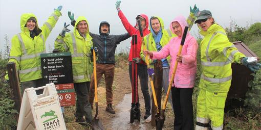 Volunteers in rain gear celebrate their hard work on the Coastal Trail.