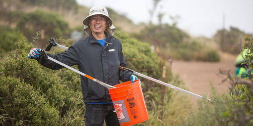 A volunteer holds a bucket and debris grabbing tool on a trail.