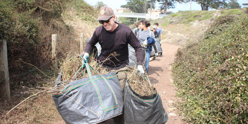 A volunteer carries large bags of vegetation while walking on a trail