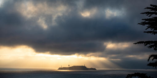 Sunlight breaking through stormy cloud over Alcatraz