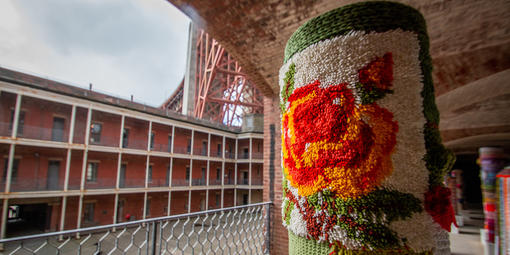 Pole covered in yarn with Fort Point and Golden Gate Bridge in background.