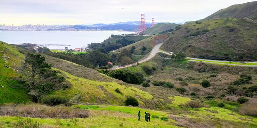 Three people stand on a hillside overlooking the Golden Gate Bridge
