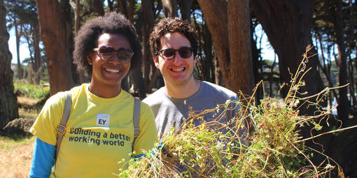 two people smile for the camera while holding plants they removed during a volunteer event