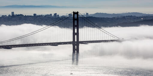Golden Gate bridge in a layer of fog with a view of San Francisco behind it.