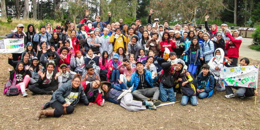A large group of cheerful teenagers excitingly cheer at Rob Hill Campground in the Presidio of San Francisco