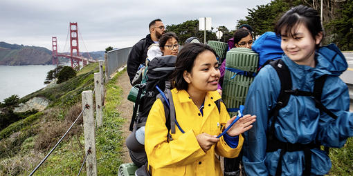 middle schoolers hike on coastal bluffs with golden gate bridge