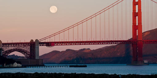 The moon rises above the bridge