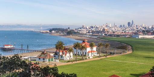 Aerial view of Crissy Field, buildings, the Warming Hut, palm trees, the golden gate, bay, and San Francisco city skyline.