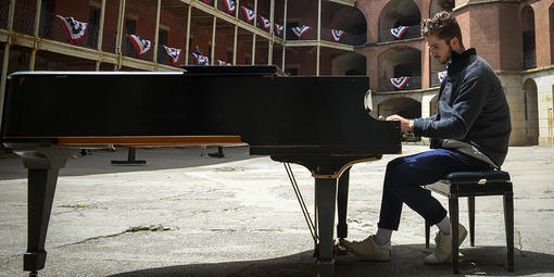 Pianist plays piano surrounded by the red-bricked Fort Point.