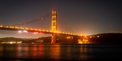The Golden Gate Bridge lit up at night.