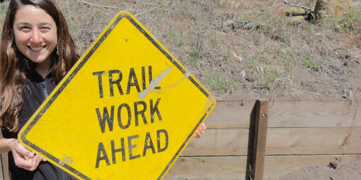 """woman holding sign that says """"Trail Work Ahead"""""""